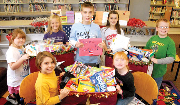 Pictured far left and moving clockwise are Mary Hunt-Feltner, Keilie Adams, Jordan Landers, Allison Klaiber, Adam Rhodes, Michaela Pugh and Victoria Bolen displaying items collected and made to be given to soldiers away from home.