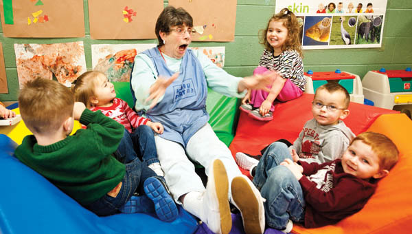 Sadie Mulkey teaches interactive reading with children in the toddler room.
