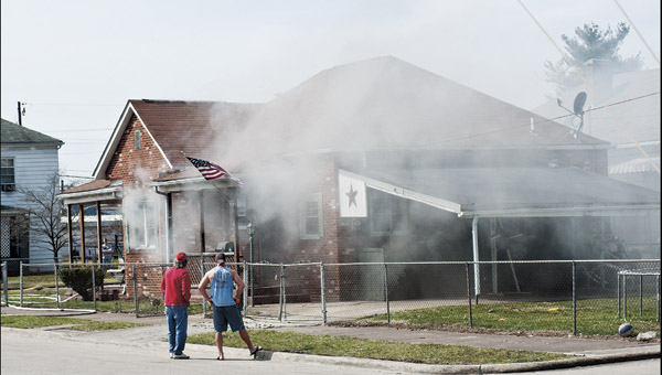 THE TRIBUNE/JESSICA ST JAMES Two local residents stand along Ashtabula Street, in Ironton, as they watch a neighborhood home on fire Sunday. The fire started before 2 p.m. at 403 Ashtabula St. No one was home at the time of the fire.