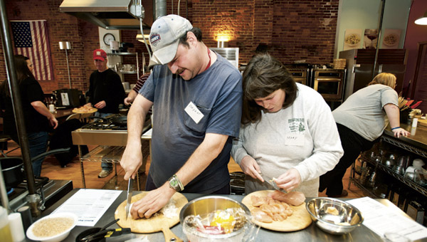 Bryant Harshbarger, left, and Mary Ruth Stephenson, right, work together as they cook up Haitian-style chicken and rice during a cooking class at the Huntington's Kitchen.