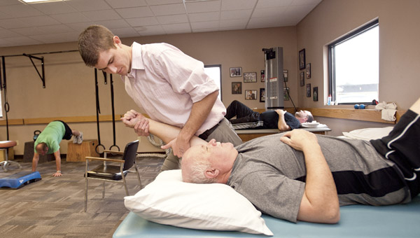 Chase Higgins, physical therapy assistant, works on a patient at Tri-State Rehab Services on South Third Street in Ironton.