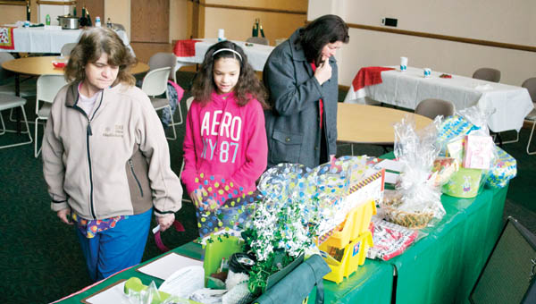 Faye Hammond, left, and her daughter Jazmine, center, check out themed gift baskets up for bid for a silent auction that was held as part of the ACTION Psychology Club's annual Chili Cook-off Thursday in the Ohio University Southern Riffe Rotunda in Ironton.