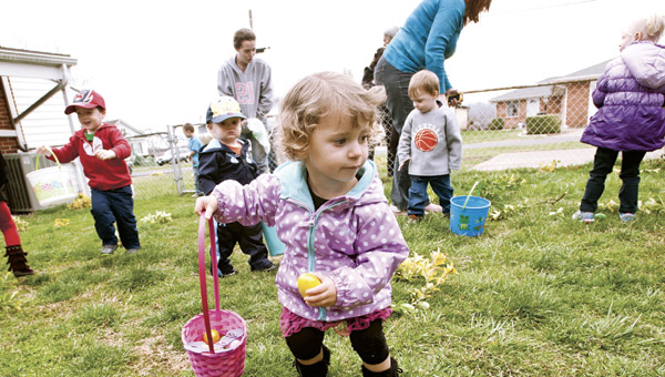 Two-year-old Sarah Case scurries around picking up eggs during Easter Fun Day event.