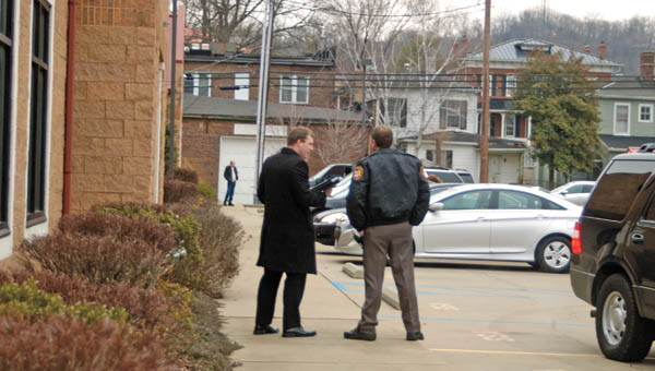 Matt Donahue from the Ohio Attorney General's Office and Lawrence County Sheriff Jeff Lawless confer in the parking lot of the Pinnacle Wellness and Longevity Center, 407 S. Third St., Suite B, Ironton. The wellness center, suspected of being an alleged pill mill, has been the focus of an investigation by the office of Ohio Attorney General Mike DeWine for the past year.