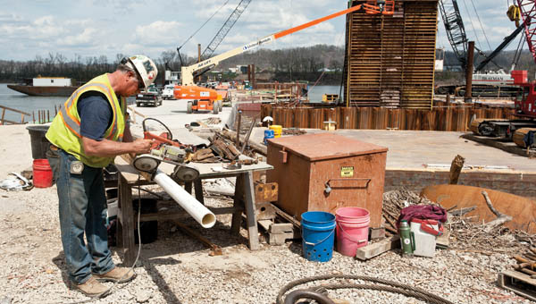 Howard Gentry cuts PVC pipe at theconstruction site for the new Ironton-Russell Bridge Wednesday.