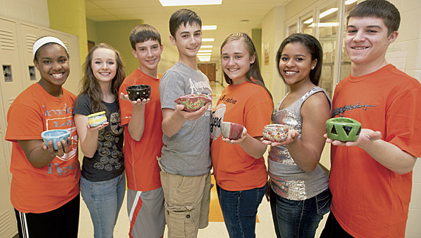 Ironton Middle School students Kara Spencer, Abby Diamond, Mitchell Weisgarber, Mason Slagel, Breanna Klaiber, Alyssa Lewis and Kyle Kleinman, pictured left to right, display their handmade ceramic bowls. About 50 IMS students made bowls to be donated to the Empty Bowls fundraiser where the proceeds from the sale of the bowls will go to the Huntington Area Food Bank.