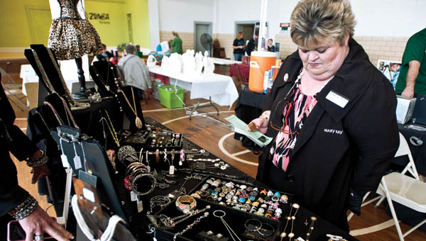 Cathy Burt, with Mary Kay, browses through a selection of Park Lane Jewelry at the booth of Cheryl Akers during the Small Business Fair Saturday morning at the Chesapeake Community Center.