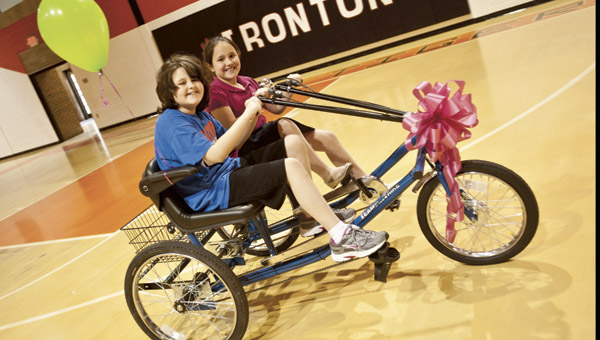 Katie Scott rides her new two-seat bike with Meredith Humphreys Thursday at the Conley Center. Scott, who just turned 10 years old, received the bike as part of a fundraising effort by students which has caused her to lose sight. Katie was diagnosed with a brain tumor at seven months old.