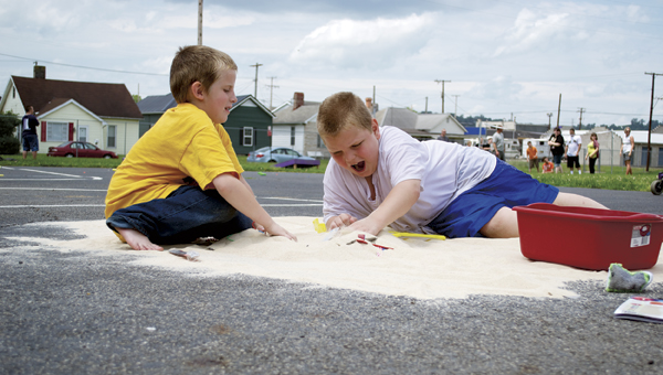 Amos Bryant, right, digs in sand for treasure with his friend during the Open Door School's Fun Day on Wednesday.