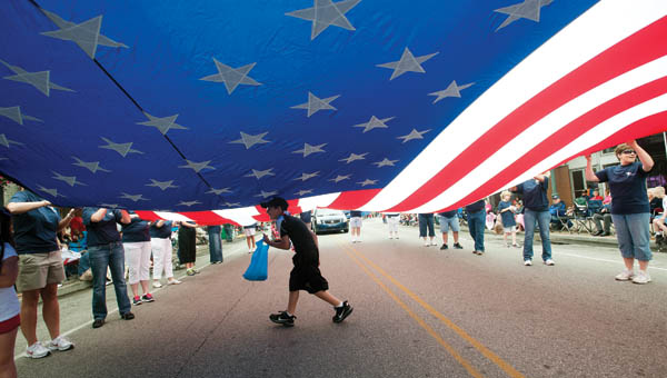 Employees with Our Lady of Bellefonte carry a huge American flag.