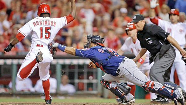 Cincinnati's Derrick Robinson (15) is tagged out at home by Cleveland catcher Carlos Santana during the seventh inning of Tuesday's game. The Reds won 8-2. (Photo Courtesy of The Cincinnati Reds)