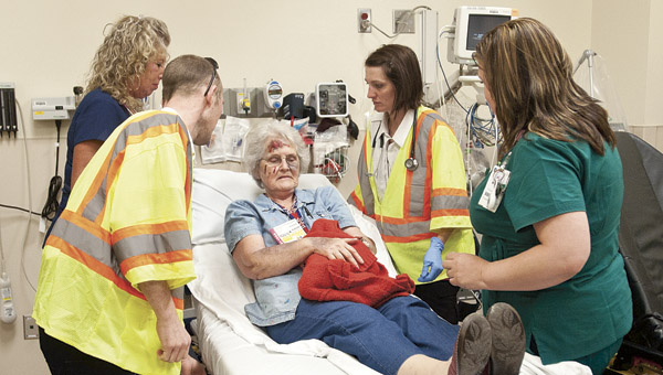 ) Jo Boggs is brought in by emergency personnel following a mock disaster Saturday morning.