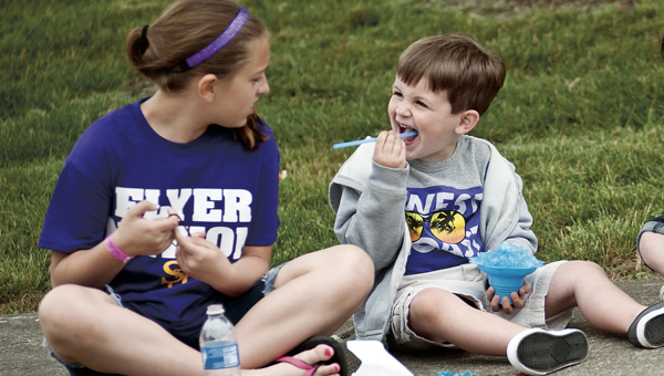 Wyatt Brown, left, makes funny faces at his babysitter, Maddie Heighton, while enjoying his snowcone at the annual Charity Fair Saturday.