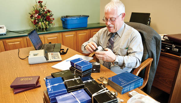Rich Giedroyc a numismatist with HCC Inc., a rare coin management company, evaluates a large collection of coin sets, Liberty dollars, silver dimes and nickels along with collectors medallions and much more to determine their value Tuesday afternoon at WesBanco in Proctorville.