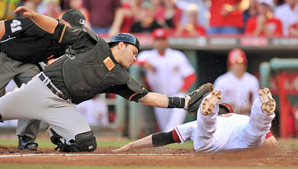 Cincinnati's Zack Cozart (rght) is ruled out at home as Pittsburgh catcher Russell Martin attempts tag the runner and end the second inning. The Reds rallied and beat Pittsburgh 2-1 in 13 innings. (Photo Courtesy of The Cincinnati Reds)