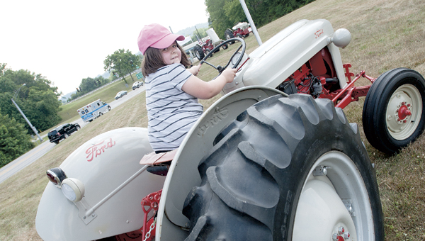 Madison Colegrove, of Ironton, takes a ride on her dad's Ford NAA 1953 tractor during the 2012 Antique Tractor and Engine Show at the Ironton Hills Shopping Center.