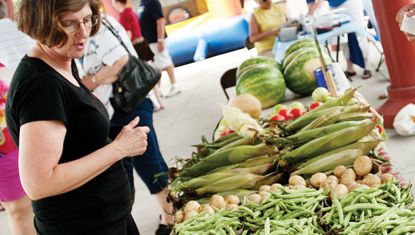 Ruth Crowe picks out some green beans and potatoes from the Roger & Tom stand at the Ironton Farmers Market Saturday in downtown Ironton.