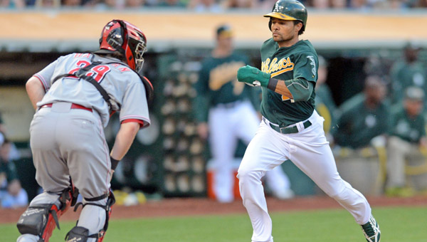 Cincinnati catcher Ryan Hanigan (29) watches as Oakland Athletics' Coco Crisp (4) scores on a single hit by Yoenis Cespedes in the second inning of Tuesday's game against the Cincinnati Reds in Oakland, Calif.. The A's beat the Reds 7-3. (MCT Direct Photo)