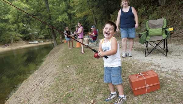 Noah Clifton breaks out into laughter, while mother Ruthie watches, at last fall's Izaak Walton Fishing Derby in Aid Township.