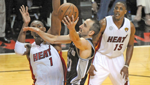 The San Antonio Spurs' Manu Ginobili, middle, goes up for a shot against the Miami heat's Chris Bosh (1) in Game 1 of the NBA Finals at AmericanAirlines Arena in Miami, Fla., on Thursday. The Spurs rallied to beat the Heat 92-88. (MCT DIrect Photo)