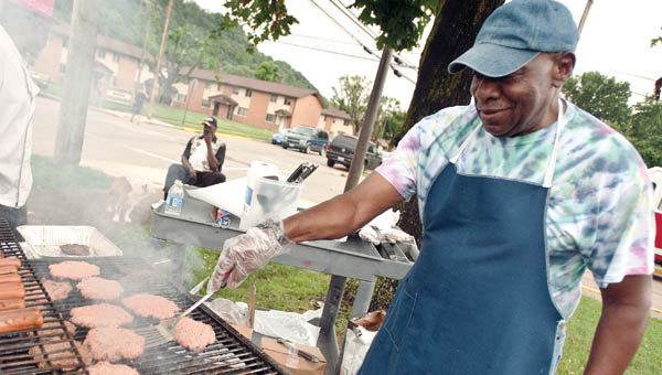 Rev. Richard Carter grills up burgers and hot dogs during the Community Health Fair Thursday.