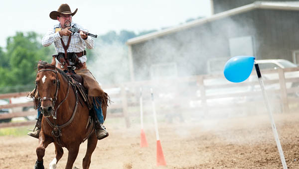 Phil Webb uses a rifle in the cowboy mounted shooting event.