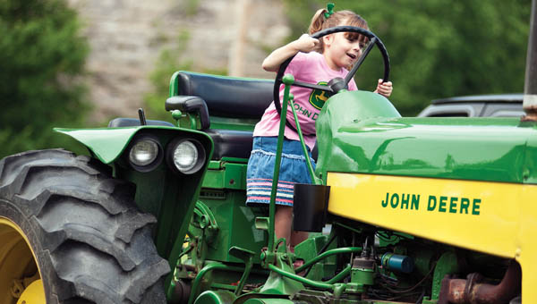Five-year-old Jayden Duncan pretends to drive her great aunt Connie Holbrook's John Deere tractor during the annual Lawrence County Ironmasters Antique Show at the Ironton Hills Shopping Plaza.