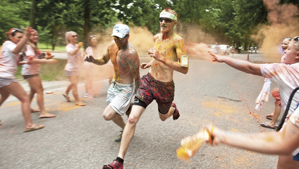 Powdered paint floats in the air as participants in the Color Splash 5K cross the finish line Saturday morning in Central Park in Ashland, Ky.