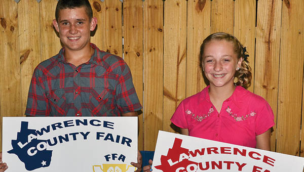 Hunter Humphreys, 13, won the grand champion trophy in the market hog show Tuesday at the Lawrence County Fair. Kara Saunders, 12, earned the reserve champion honor.