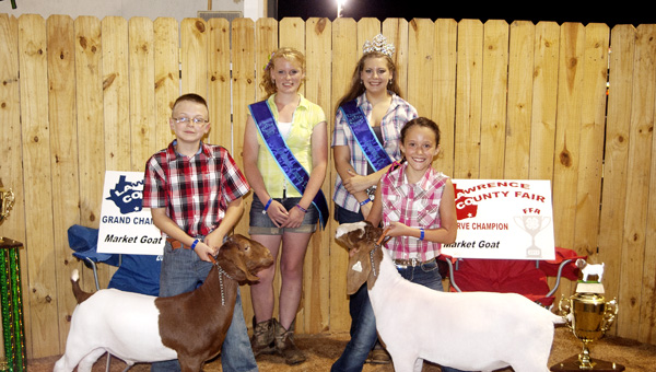 Daniel Mootz (left) takes the grand champion market goat prize Monday at the Lawrence County Fair. Lauren Wells (far right) won the reserve champion prize. Also pictured are Skye Barnett (center right), fair queen, and Hannah Williams, first runner up.