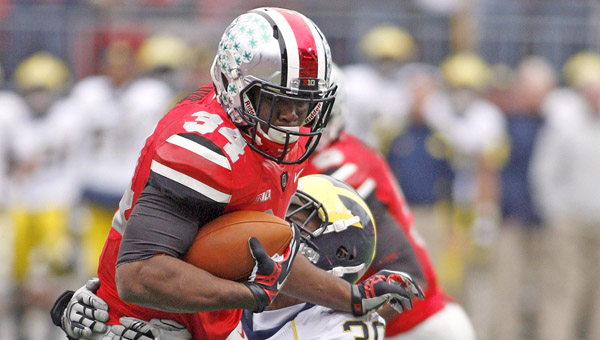 Ohio State's Carlos Hyde (34) is shown trying to break free from Michigan's Thomas Gordon (30) during the second half of a game last season. Hyde — the team's leading scorer last season — is one of four Buckeye players who were disciplined by head coach Urban Meyer for off the field legal issues. (MCT Direct Photo)