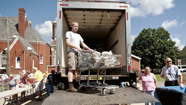 Christopher McClurg unloads sacks of potatoes off the Lutheran Social Service Mobile Food Pantry Truck Thursday morning outside of St. Paul Lutheran Church.