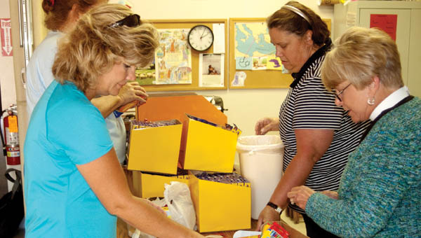 Volunteers work to fill the remaining 250 backpacks for Saturday's giveaway