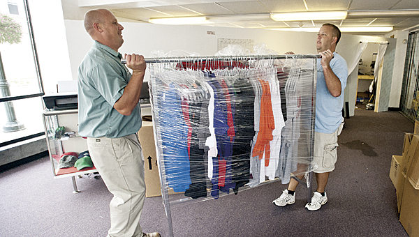 Mike Depriest, left, and Jon Ferguson, right, haul merchandise out of the Tri-State Spirit Shop following a sewer backup at the Ironton City Center.