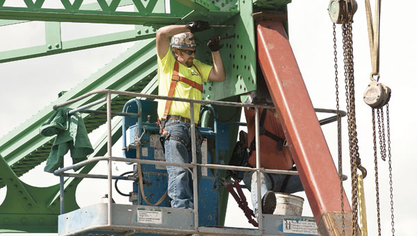 Workers remove rivets from the Ben Williamson Memorial Bridge late Saturday morning as part of the repair work to remove the damaged support beam. (BELOW) Allen Blair, public information officer for the Kentucky Transportation Cabinet, stands next to the red temporary support struts and the new green I-beam that will replace the damaged beam on the bridge.