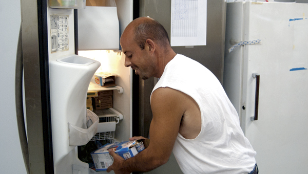 Zack Papalia, a volunteer at the food bank, gets some frozen items out of a freezer to give to recipients.