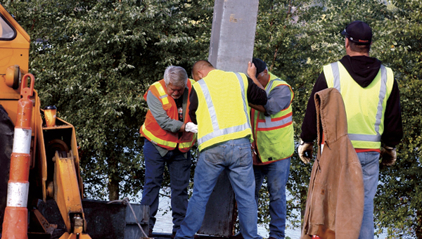 Ironton city workers work to place a steel beam into the ground at the Center Street floodgate Tuesday morning. The exercise to assemble to floodgate took about 9 hours and is mandated by the Army Corps of Engineers to be performed every three years.