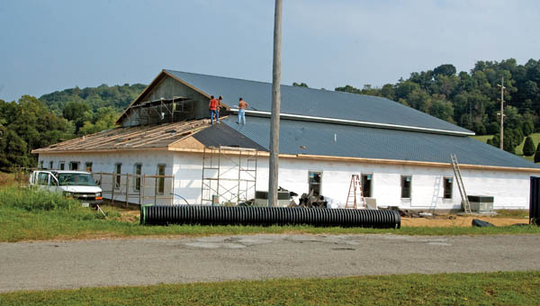 Workers continue attaching a metal roof to the new Cross Community Church in South Point.