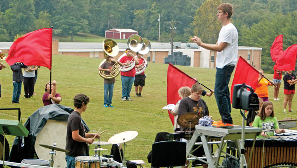 "Rock Hill High School band director Nick Basham, on the wooden platform, observes the ""Pride of Lawrence County"" during practice Wednesday.  The Redmen are preparing for Saturday's Rock Hill Band Invitational, a competition returning after a 13-year hiatus."