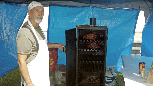 Robin Russell shows two 10-pound chunks of pork being smoked on a custom-made stoker he made in his garage. Stoker Bar-B-Que, inside Tipton's Mini Mart on State Route 93, has pulled pork and barbeque pulled pork sandwiches and sides prepared on site.