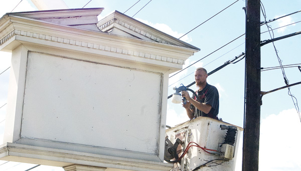 A painter from Young Signs of Ashland, Ky., paints the former Hallmark sign at the new Community Hospice office location on South Third Street in Ironton.
