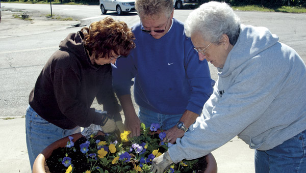 Vicki Mc Daniel, Coal Grove Mayor Larry McDaniel and Juanita Markel plant flats of pansies in one of several flower pots in the village of Coal Grove.