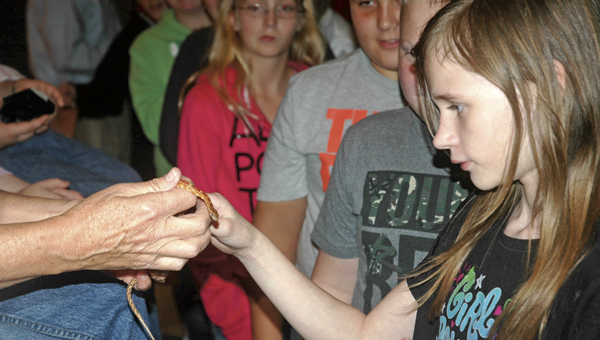 Students from Dawson-Bryant Middle School stand in line for a chance to pet a corn snake during a field trip to Raceland-Worthington High School in Kentucky.