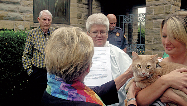 The Rev. Sallie Schisler blesses a family cat at Saturday's event.
