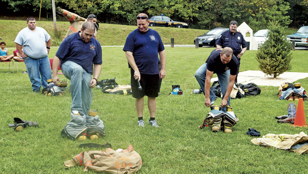 Alex Johnson of Upper Township Fire Department, left, and Austin Phillips of Harrison Fire Department in Gallipolis, right, compete in the firefighters' challenge during the Public Fire Safety Day at Paul Porter Park in Coal Grove on Saturday. Jay Sherman, Coal Grove Fire Department captain, center, looks on.