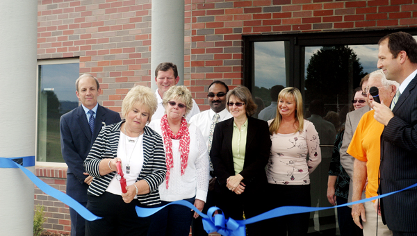 Nancy Lewis, nurse practitioner and director of health integration, development and clinical quality for the Ironton-Lawrence County Community Action Organization, cuts the ribbon at a ceremony and open house for the new Rome Proctorville Family Medical Center Monday. The facility was dedicated to Lewis for her nearly 40 years of service.