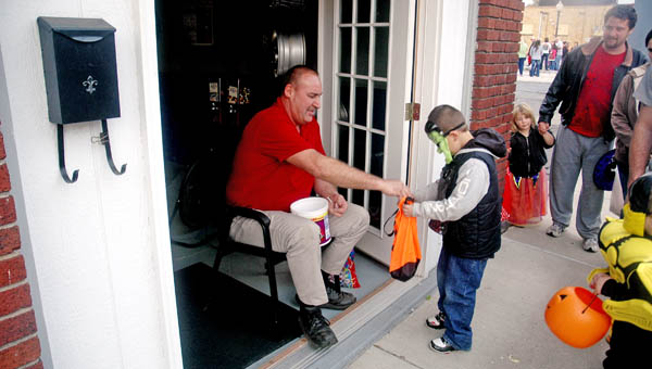Charlie Haas, owner of Charlie's Tire Sales in Ironton, hands out candy during Safe Trick or Treat on Monday.