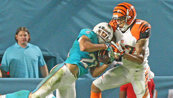 The Miami Dolphins' Brent Grimes, left, intercepts ball intented for Cincinnati Bengals' wide receiver Marvin Jones during the third quarter at Sun Life Stadium in Miami Gardens, Fla, on Thursday. Bengals' quarterback Andy Dalton was intercepted three times and sacked in overtime that gave the Dolphins a 22-20 win. (MCT Direct Photos)
