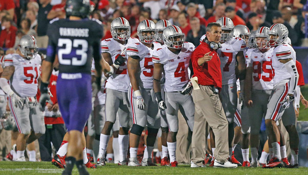 Ohio State Buckeyes' head coach Urban Meyer talks with his team on the sidelines during the Northwestern game. Meyer complained that the BCS system is flawed. (MCT Direct Photos)