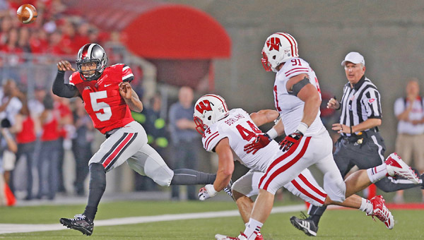 Ohio State quarterback Braxton Miller (5) throws the ball away under pressure from Wisconsin linebacker Chris Borland (44) and defensive end Konrad Zagzebski at Ohio Stadium. Miller is the key to the Buckeyes' high-powered offense this season. (MCT Direct Photo)